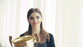 Portrait of pretty girl with golden glowing trophy cup looking at window 4K.  stock video