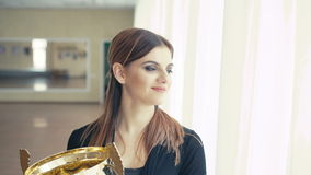 Portrait of pretty girl with golden glowing trophy cup looking at window 4K.  stock video footage