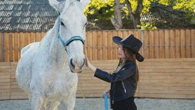 Portrait of pretty girl in the hat caressing with smile a white horse stock footage
