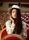Portrait of a pretty girl hipster in a movie theater wearing hat, dreaming alone Royalty Free Stock Photos