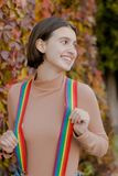 Portrait of pretty girl holding multicolored suspenders royalty free stock photography