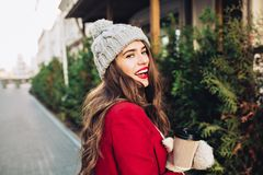 Portrait pretty girl with long hair in red coat walking on street with coffee to go. She looks excited to camera. royalty free stock photography