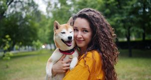 Portrait of pretty girl loving dog owner standing in park with her beautiful pet smiling