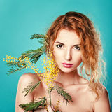 Portrait of a pretty girl with mimosa flowers. Spring. Stock Photography