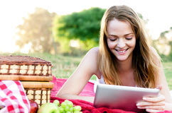 Portrait of pretty girl in park with her tablet computer Royalty Free Stock Images