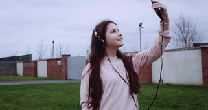 Portrait of pretty girl in pink vest with headphones doing selfie in front of brick fence. Red Epic camera shot in 4k. stock video