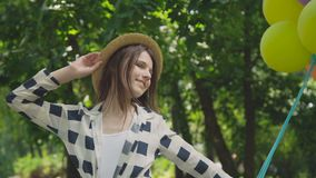 Portrait of pretty girl poses at camera with colourful balloons in sunny park stock video footage