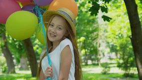 Portrait of pretty girl poses at camera with colourful balloons in sunny park stock footage