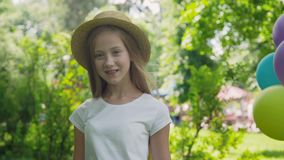 Portrait of pretty girl poses at camera with colourful balloons in sunny park stock video