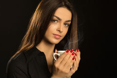 Portrait of a pretty girl posing on a black with cup of coffee Stock Images