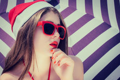 Portrait of a pretty girl in Santa Claus hat and red sunglasses Royalty Free Stock Image