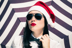 Portrait of a pretty girl in Santa Claus hat and sunglasses. With bright painted lips next to striped background royalty free stock photo