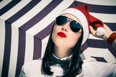 Portrait of a pretty girl in Santa Claus hat and sunglasses. With bright painted lips next to striped background royalty free stock image