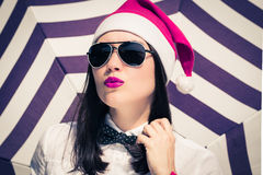 Portrait of a pretty girl in Santa Claus hat and  sunglasses Royalty Free Stock Photo