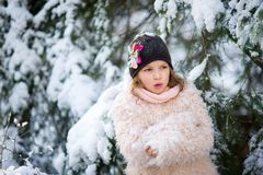 Portrait of the pretty girl of school age against the background of a snow-covered fir-tree. Royalty Free Stock Photos