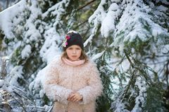 Portrait of the pretty girl of school age against the background of a snow-covered fir-tree. Stock Photos