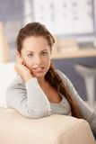 Portrait of pretty girl sitting on sofa smiling Stock Image