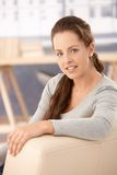 Portrait of pretty girl sitting on sofa smiling Stock Photography