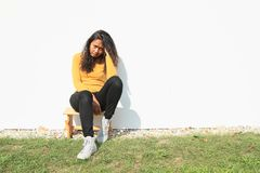 Portrait of pretty girl sitting on wooden grinder. Portrait of pretty Papuan girl with curly hair dressed in yellow t-shirt, black pants and white shoes - sad Stock Photo