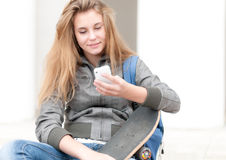 Portrait of pretty girl with skateboard outdoor. Stock Photos