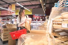 Portrait of a pretty girl standing in the bread department of a supermarket with a paper package. Girl in a red basket, thanked for shopping in his hands, buys stock photography