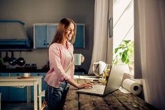 Portrait of pretty girl standing in the kitchen keyboarding on laptop, holding cup. Stock Image
