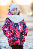Portrait of pretty girl standing in winter clothes with scarf and hat Royalty Free Stock Photo