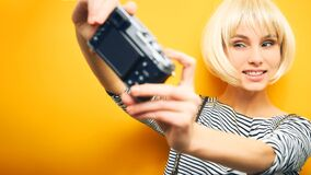 Portrait of a girl in a striped sweater and a white wig makes a selfie on a camera on an orange background