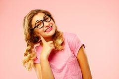 Portrait of a pretty girl student wearing glasses over pink back. Portrait of a pretty girl student wearing glasses Stock Photo