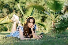 Portrait of an pretty girl in summer clothes listening to music with yellow headphones while holding mobile phone on the stock image