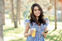 Portrait of an pretty girl in summer clothes listening to music with yellow headphones while holding mobile phone royalty free stock image