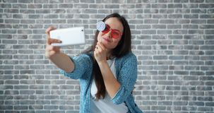 Portrait of pretty girl taking selfie with smartphone camera holding lollipop. And posing with candy on brick wall background. Youth and self portrait concept stock video footage