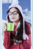 Portrait of pretty girl with tea cup. Young hispanic girl drinking hot tea while wearing warm clothes at home with winter background Stock Photography