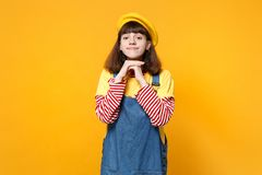 Portrait of pretty girl teenager in french beret, denim sundress holding hands near face isolated on yellow wall. Background in studio. People sincere emotions stock image