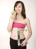 Portrait of pretty girl wearing sports clothes holding scales and a measuring tape with green apple Royalty Free Stock Photos