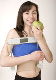 Portrait of pretty girl wearing sports clothes holding scales and a measuring tape with green apple Stock Image