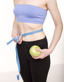 Portrait of pretty girl wearing sports clothes holding scales and a measuring tape with green apple Stock Photography