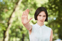 A portrait of a pretty girl in a white blouse on a natural background. Beautiful young woman holding her hand in rejection. stock photography