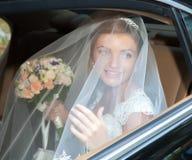 Portrait of a pretty bride in a car Stock Photos