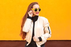 Portrait of pretty hipster girl in sunglasses on orange background. Perfect summer make-up and style royalty free stock photography