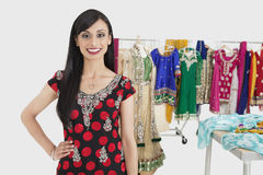 Portrait of pretty Indian female dressmaker standing with hand on hip Stock Photo