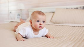 Portrait of pretty infant in white clothes on a bed at home stock video footage