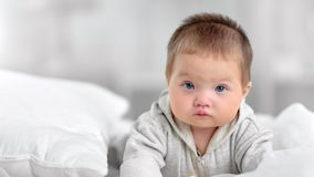 Portrait of pretty innocence little baby with blue eyes posing at white bedroom interior. Medium close-up. Face of beautiful healthy cute child enjoying morning stock video