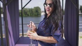 Portrait of pretty joyful young woman with a lovely smile dancing a cocktail outdoors. Leisure of beautiful sensual lady. Portrait of pretty joyful woman with a stock video footage