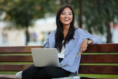 Portrait of a pretty laughing asian female student sitting. With a laptop computer on the bench at the park Royalty Free Stock Images