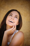 Portrait of pretty laughing young. Portrait of beautiful laughing young brunette woman propping up her face and looking up against beige background Stock Photos