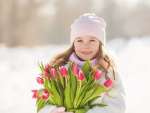 Portrait pretty little baby girl with a tulips in a hands in the winter sunny day Royalty Free Stock Image