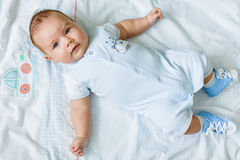 Portrait of a pretty little baby , lying on a light blanket royalty free stock photography