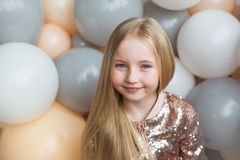 Portrait of pretty little blonde girl on a balloons background Royalty Free Stock Image