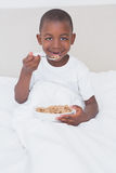 Portrait of a pretty little boy eating cereals in bed Royalty Free Stock Image